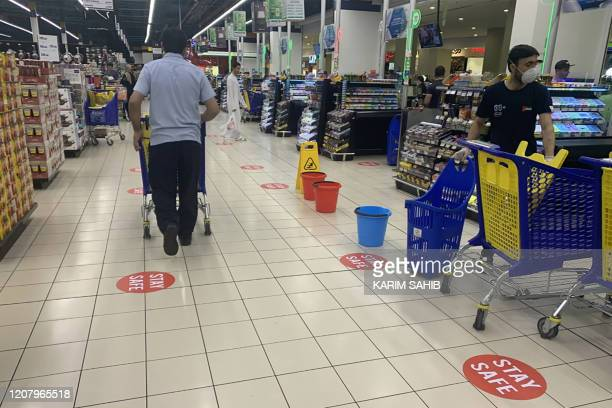 "This picture taken on March 22, 2020 in Dubai shows a view of distance stickers reading ""stay safe"" placed along aisles at a supermarket, marking..."