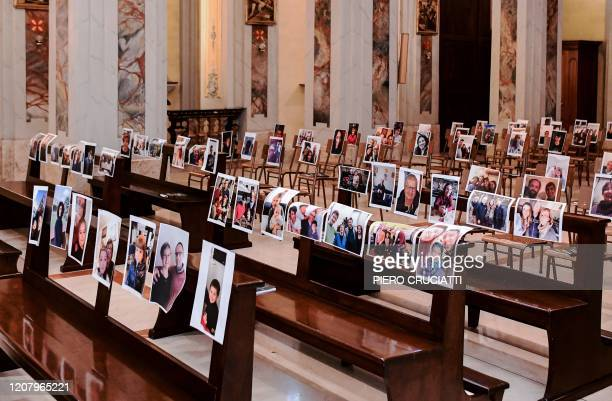 This picture taken on March 22 2020 shows the empty Church of Robbiano during the Sunday mass with selfie photographs sent to Don Giuseppe Corbari...