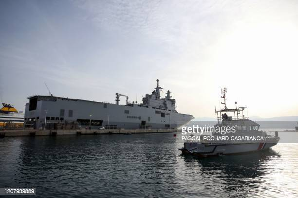 This picture taken on March 22 shows a French gendarme patrol boat and the helicopter-carrier 'Tonnerre' of the French Marine Nationale docked in the...