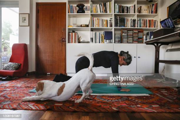 This picture taken on March 23, 2020 shows a woman taking part in an online pilates class at home, as her dog Elvis stretches next to her, in...