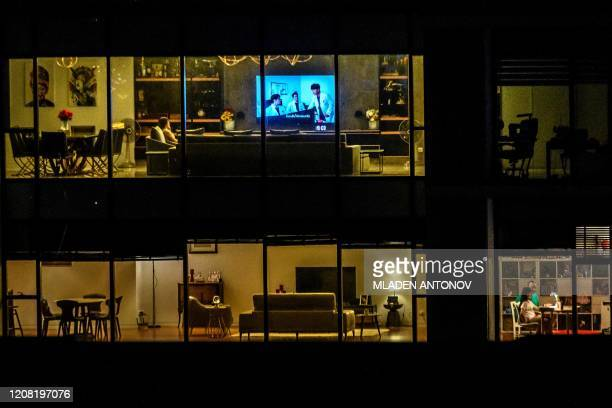 TOPSHOT This picture taken on March 23 2020 shows people in their apartments amid fears over the spread of the COVID19 novel coronavirus in central...