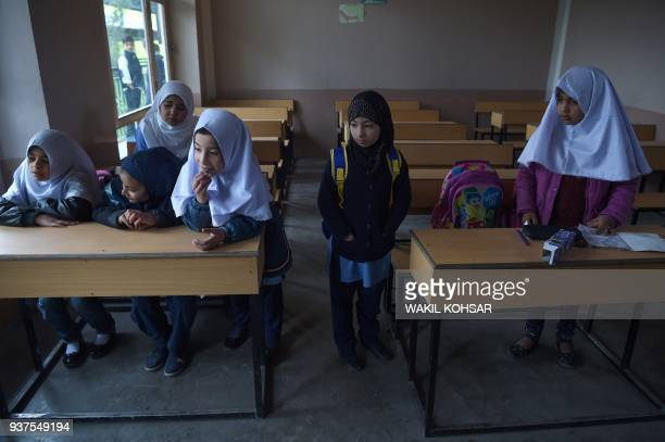 TOPSHOT This picture taken on March 24 2018 shows Afghan schoolgirl Dunya attending class with other students on the first day of school for the year...