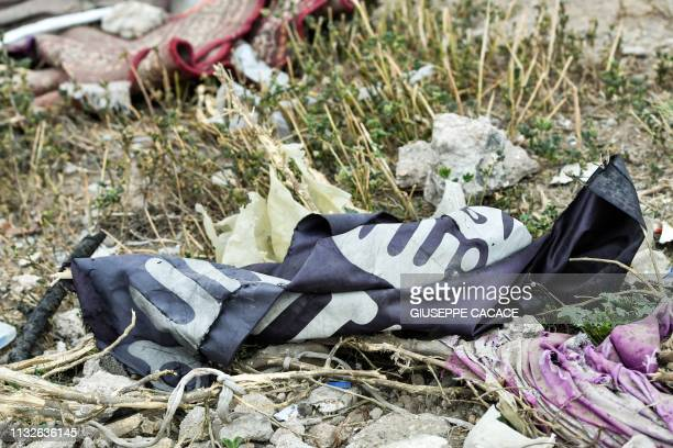 This picture taken on March 24, 2019 shows a discarded Islamic State group flag lying on the ground in the village of Baghouz in Syria's eastern Deir...