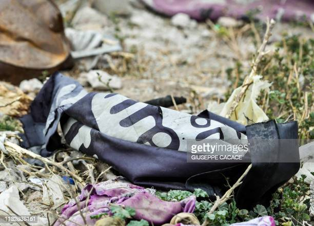 This picture taken on March 24 2019 shows a discarded Islamic State group flag lying on the ground in the village of Baghouz in Syria's eastern Deir...