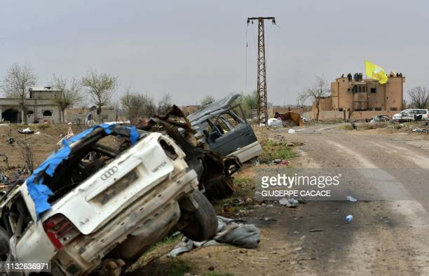 This picture taken on March 24 2019 shows destroyed vehicles lying in a ditch on the side of a road with the Syrian Democratic Forces unfurled flag...