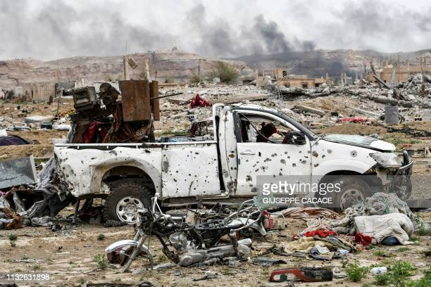 TOPSHOT This picture taken on March 24 2019 shows smoke rising behind destroyed vehicles and damaged buildings in the village of Baghouz in Syria's...