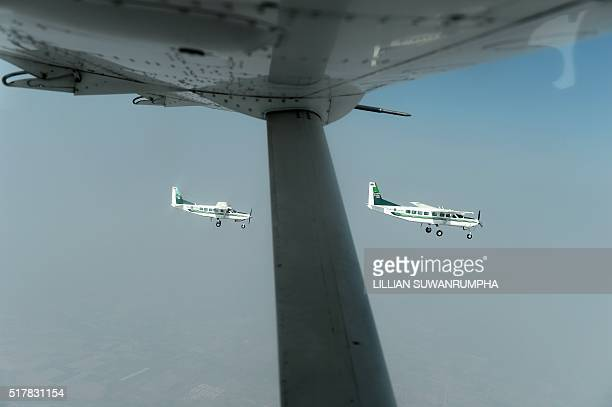 This picture taken on March 25 2016 shows a pair of Cessna 208 Caravan aircraft from the Thai Department of Royal Rainmaking flying above Nakhon...