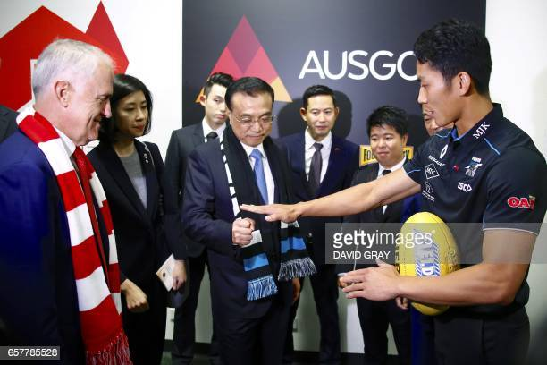This picture taken on March 25 2017 shows Australia's Prime Minister Malcolm Turnbull and China's Premier Li Keqiang speaking with Port Adelaide's...