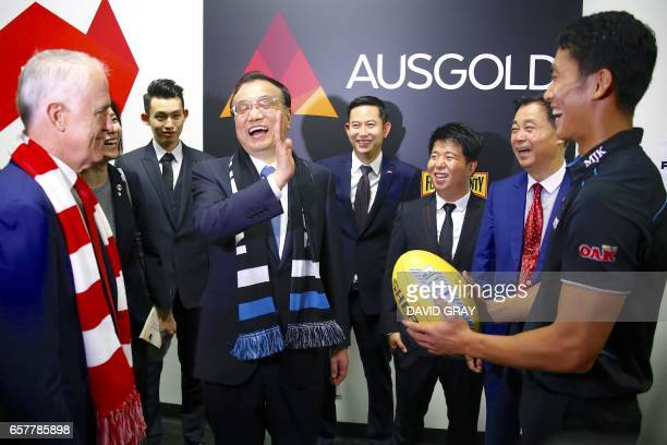 This picture taken on March 25 2017 shows Australia's Prime Minister Malcolm Turnbull and China's Premier Li Keqiang laughing with Port Adelaide's...