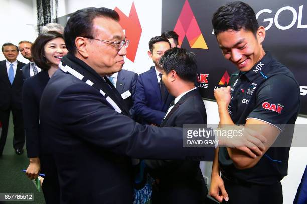 This picture taken on March 25 2017 shows China's Premier Li Keqiang touching the arm of Port Adelaide's Chen Shaoliang the Australian Rules football...