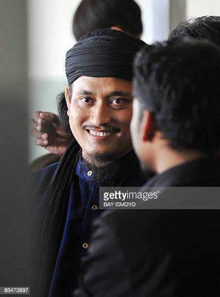This picture taken on March 26 2008 shows Imam Samudra one of the three convicted Bali bombers talking to unidentified men inside Batu prison on the...