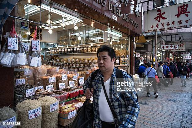 This picture taken on March 26 2016 shows a man walking past a shop selling dried seafood products along a street in Hong Kong Mexico is fighting to...