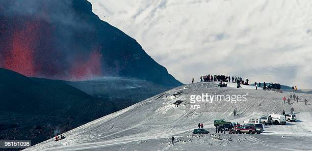 This picture taken on March 27, 2010 shows tourists gathered to watch lava spurt out of the site of a volcanic eruption at the Fimmvorduhals volcano...