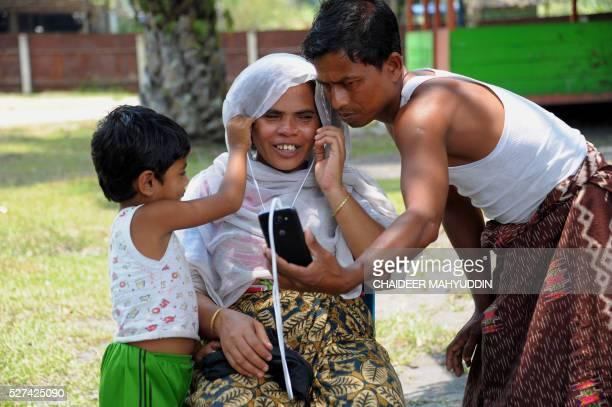 TOPSHOT This picture taken on March 27 2016 shows a Rohingya family doing a video call with their family at the Rohingya housing complex in Bayeun in...
