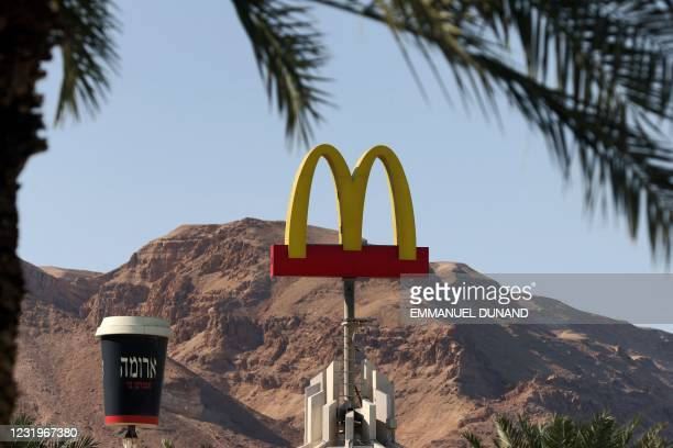 """This picture taken on March 27, 2021 shows a view of a McDonald's restaurant's iconic """"golden arches"""" logo next to a giant coffee cup of its """"Aroma""""..."""