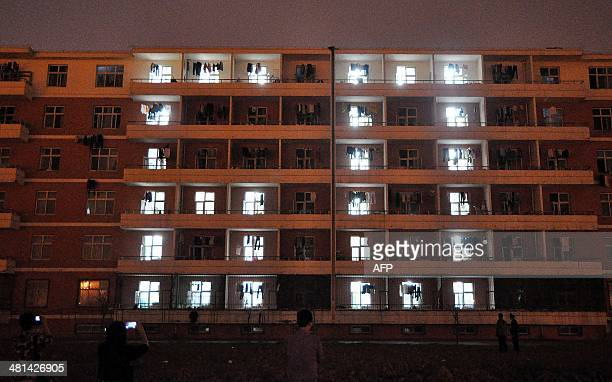 This picture taken on March 28, 2014 shows students taking pictures of their dormitory after lights are switched in recognition of 'earth hour' at a...