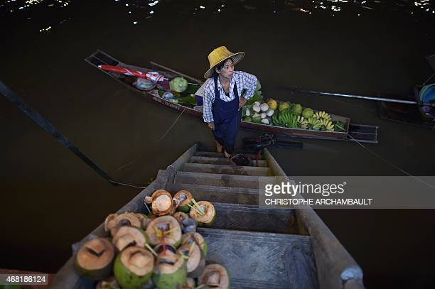 This picture taken on March 28 2015 shows a fruit vendor waiting for customers beside her boat moored along the Amphawa canal a small tributary of...