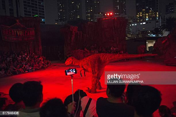 TOPSHOT This picture taken on March 28 2016 shows people watching a show at Dinosaur Planet a recentlyopened educational theme park in Bangkok / AFP...
