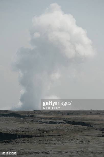 This picture taken on March 28 2016 shows white smoke spewing from the centre of a mud volcano area in Sidoarjo East Java A mud volcano that erupted...