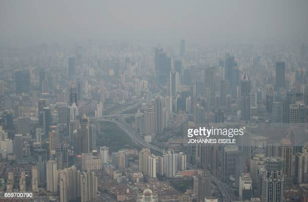 This picture taken on March 28 2017 shows residential buildings amid smog in Shanghai / AFP PHOTO / Johannes EISELE