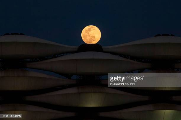 """This picture taken on March 28, 2021 shows a view of the rising full """"Worm Moon"""" above Basra International Stadium in the southern Iraqi city."""