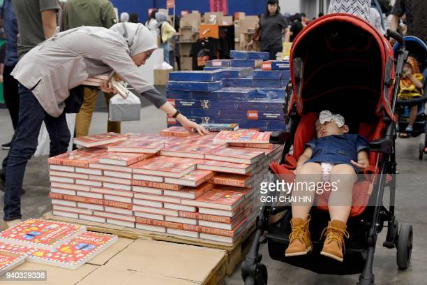 This picture taken on March 30 2018 shows a woman looking at books as a child sleeps in a pram at the Big Bad Wolf book sale in Serpong in the...