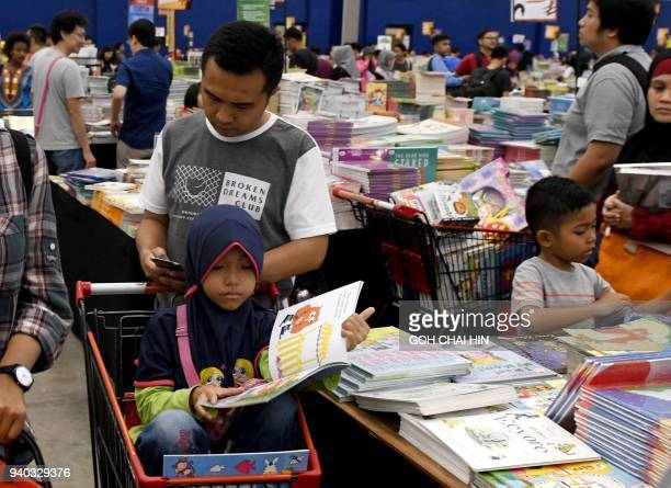 This picture taken on March 30 2018 shows families browsing through books at the Big Bad Wolf book sale in Serpong in the suburbs of Jakarta / AFP...