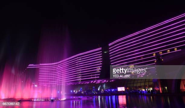 """This picture taken on March 31, 2017 shows the """"dancing fountain"""" in front of the main building of Okada casino during the fountain's launch at..."""
