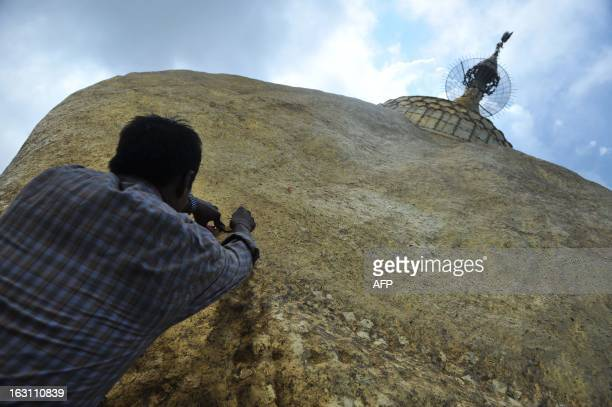 This picture taken on March 4 2013 shows a Buddhist devotee applying a gold leaf on the Kyaikhtiyo pagoda in Myanmar's eastern Mon state A wellknown...