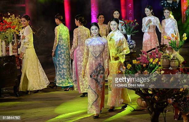 This picture taken on March 4 2016 shows models presenting creations of Vietnam's traditional dress 'ao dai' during a fashion show held at the temple...