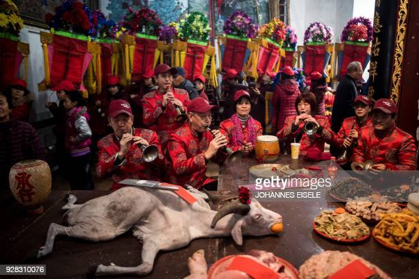 TOPSHOT This picture taken on March 4 2018 shows villagers playing music next to the offering table for a local Taoist sea deity in Huangqi village...