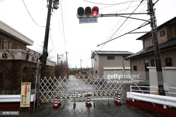 This picture taken on March 5 2018 shows a closed gate to prevent people from entering the exclusion zone in Futaba town Fukushima prefecture as...