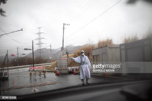 This picture taken on March 5 2018 shows a guard gesturing at a checkpost exit from the exclusion zone of Futaba town Fukushima prefecture as Japan...