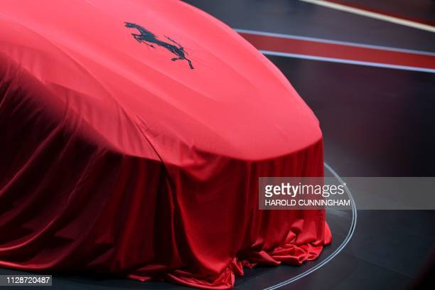 This picture taken on March 5 2019 shows a Ferrari covered up during a press day ahead of the Geneva International Motor Show in Geneva The 2019...