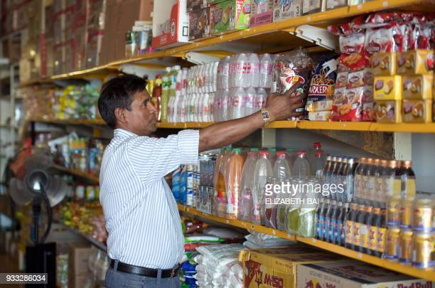 This picture taken on March 6 2018 shows Rohingya refugee Kobir Ahmed working inside a grocery store in Melbourne Kobir helps run a grocery store in...
