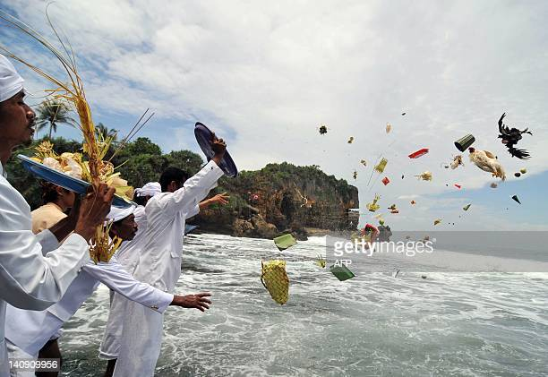 This picture taken on March 7 2012 shows Hindu devotees throwing their offerings during the Melasti ceremony in Gunung Kidul Yogyakarta The Melasti...
