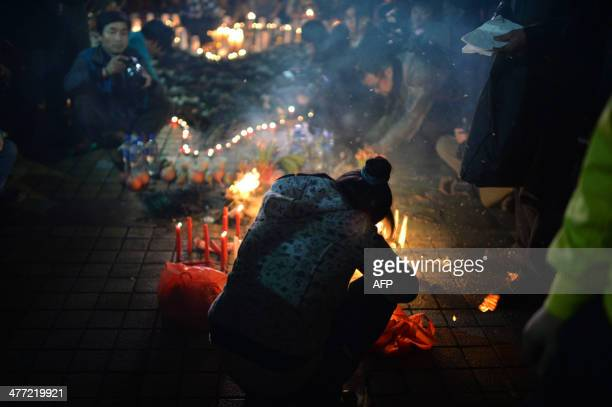 This picture taken on March 7, 2014 shows mourners burning joss money and incenses at the scene of the terror attack at the main train station in...