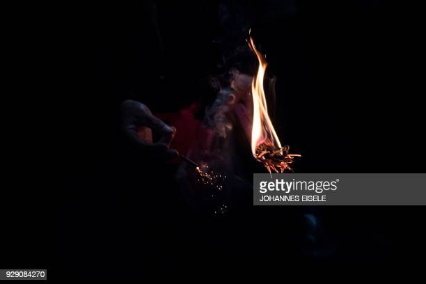 This picture taken on March 7 2018 shows a man using burning incense to light a fire cracker in a temple before the start of the eating flowers...