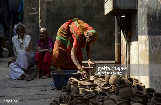 This picture taken on March 7 2019 shows an Indian woman arranging clay pots for drying in Dharavi Asia's largest slum in Mumbai Residents of Asia's...