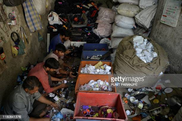 This picture taken on March 7, 2019 shows Indian workers sorting plastic at a factory in Dharavi, Asia's largest slum in Mumbai. - Residents of...