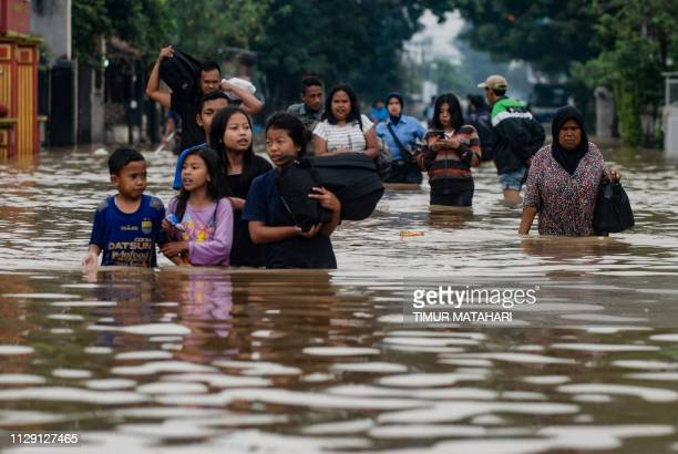 This picture taken on March 7, 2019 shows residents walking along a flooded road as they evacuate Dayeuhkolot village in Bandung, West Java province....