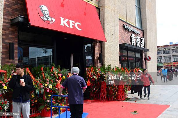 This picture taken on March 8 2015 shows people walk past a KFC fast food restaurant in Lhasa southwest China's Tibet Autonomous Region US fast food...