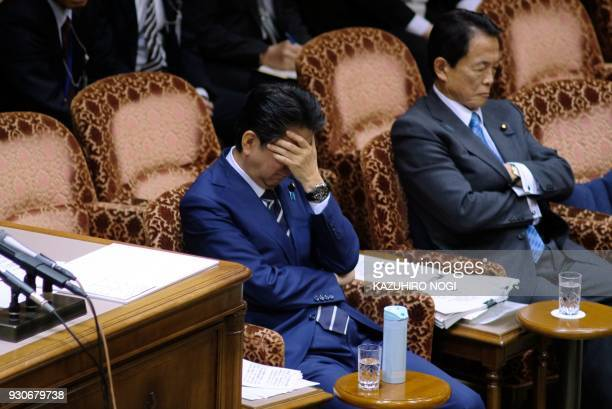 TOPSHOT This picture taken on March 8 2018 shows Japan's Prime Minister Shinzo Abe and Finance Minister Taro Aso attending an upper house budget...