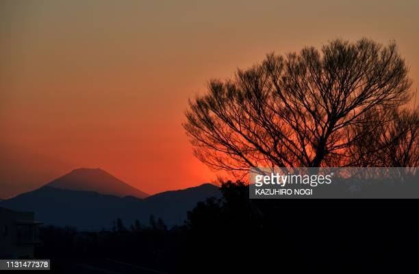TOPSHOT This picture taken on March 8 2019 shows Japan's highest mountain Mt Fuji during sunset near the Yokohama International Stadium one of the...