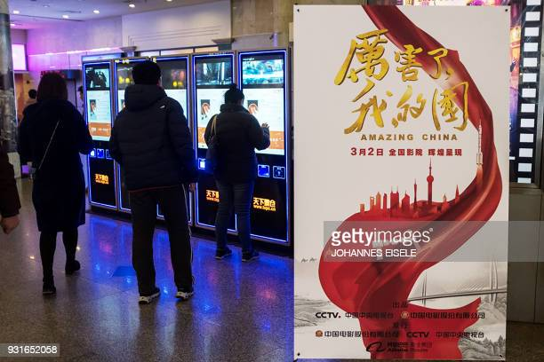 This picture taken on March 9 2018 shows a poster for the film 'Amazing China' at a cinema hall in Shanghai Citizens across China are being corralled...