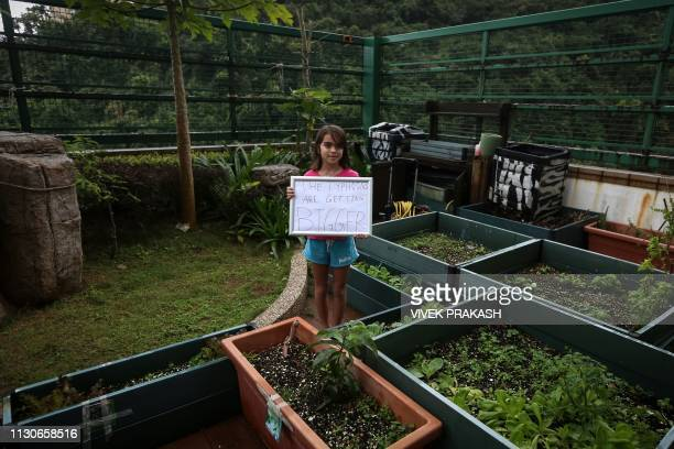 This picture taken on March 9 2019 shows Cally Nolasco posing for a photograph with a sign containing an environmental message in Hong Kong Thousands...