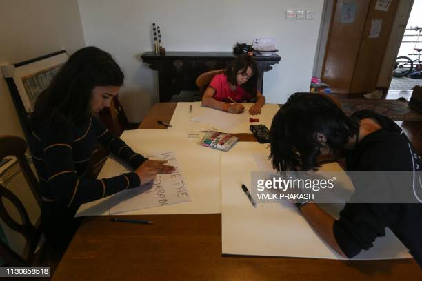 This picture taken on March 9 2019 shows Ella Nolasco Cally Nolasco and Michael Nolasco preparing signs containing environmental messages at their...