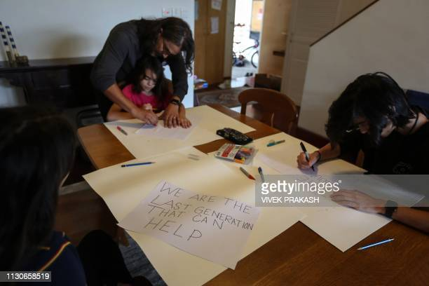 This picture taken on March 9 2019 shows Joe Nolasco helping his children Ella Cally and Michael prepare signs containing environmental messages in...