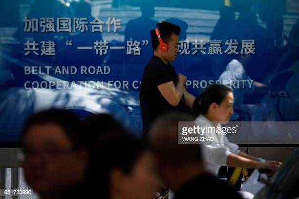 This picture taken on May 10 2017 shows a man wearing headphones walking past a poster at a bus station ahead of the Belt and Road Forum for...
