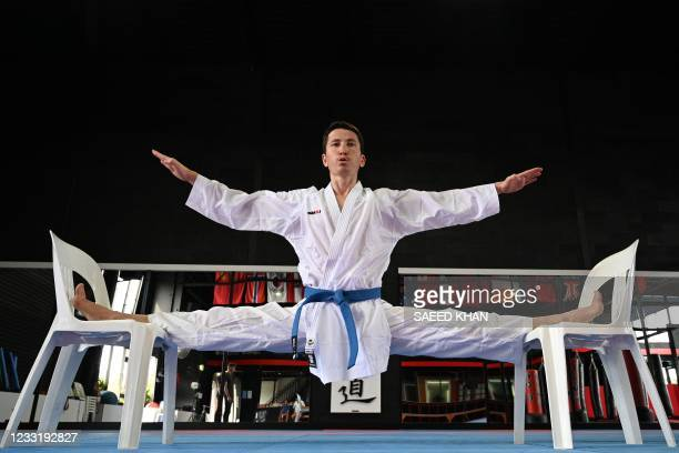 This picture taken on May 11, 2021 shows Afghan-born refugee and karate competitor Asif Sultani stretching as he trains at a gym on the outskirts of...